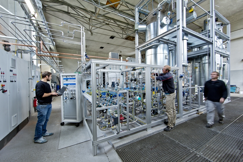 ZSW-Forscher bei der Kontrolle der Gasmischung. Im Hintergrund die Methanisierungsanlage.Foto: Zentrum für Sonnenenergie- und Wasserstoff-Forschung Baden-Württemberg (ZSW)