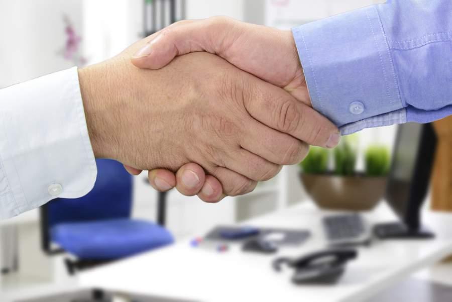 Hande beim Vertragsabschluss im Büro, Verkäufer freut sich zusammen mit dem Käufer über den erfolgreichen Abschluss