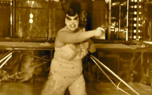 Crossover, maskierte Frau ballt die Faust.