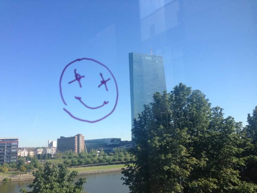 Smiley an einem Fenster gemalt mit Blick auf Frankfurter EZB Zentrale, Symbol für happy sein