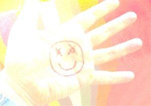 Happy, ein Mann hat sich einen Smiley auf die Hand gemalt
