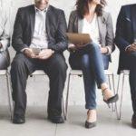 Bewerber sitzen nebeneinandergereicht auf Stühlen, Gesichter sind nicht zu erkennen. Durch Recruiting mit DiSG® lernen Unternehmen die Bewerber wirklich kennen