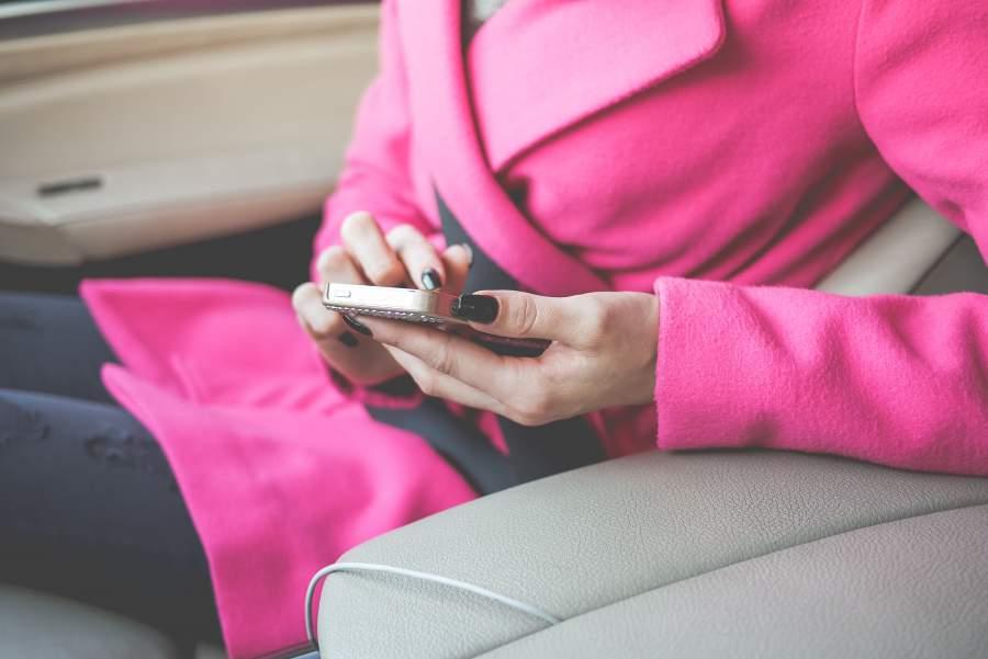 Frau in rosa Mantel nutz ihr Smartphone in einem Auto