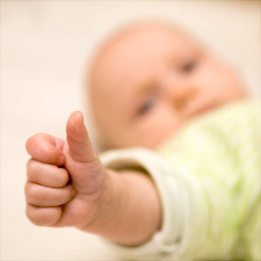 Baby mit gestrecktem Daumen, Symbol für Ziele, die einem wirklich wichtig sind