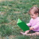 Kind im rosa Pullover und kurzen blauen Hosen sitz im Gras und erwirbt Wissen indem es ein Buch liest