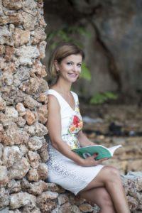 Bild von Jaqueline Bakir Brader mit ihrem Buch die Mutmacherin vor einem Baum