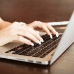 Junge Frau erstellt am Notebook einen Newsletter fuer das E-Mail-Marketing ihres Unternehmens