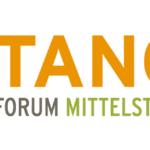 Weisse Wohn Immobilie auf gruenem Grass vor orangefarbenem Himmel