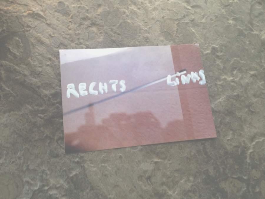 Rote Karte vor braunem Hintergrund auf dem die Worte Rechts und Links stehen