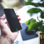 Junger Mann haelt Smartphone in der Hand und nutzt mobiles Internet