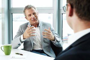 Andreas Enrico Brell im Gespraech mit einem seiner Kunden derm er versucht einen entspannten Umgang mit Geld beizubringen
