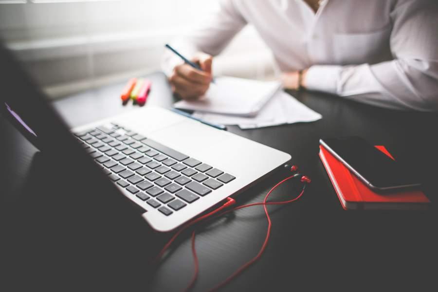 Kaltakquise, Telefonakquise, Positionierung, Laptop, ARbeitsplatz, Schreibtisch, Block, Stift, Skizzen, Notizen, Kopfhörer, Ohrstöpsel, Arbeit, Business, Haltung