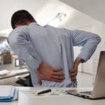 Rückenschmerzen, Arbeitsplatz, Gesundheit im Büro, Schreibtisch, Laptop, Unterlagen, Mann, Büro