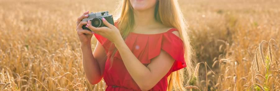 Bild, Kamera, Fotokamera, analog, Mädchen, Frau, lange Haare, rotes Oberteil, rotes Kleid, Feld, Natur, Sonne, Lichteinfall, Authentizität, nofilter, authentisches Marketing