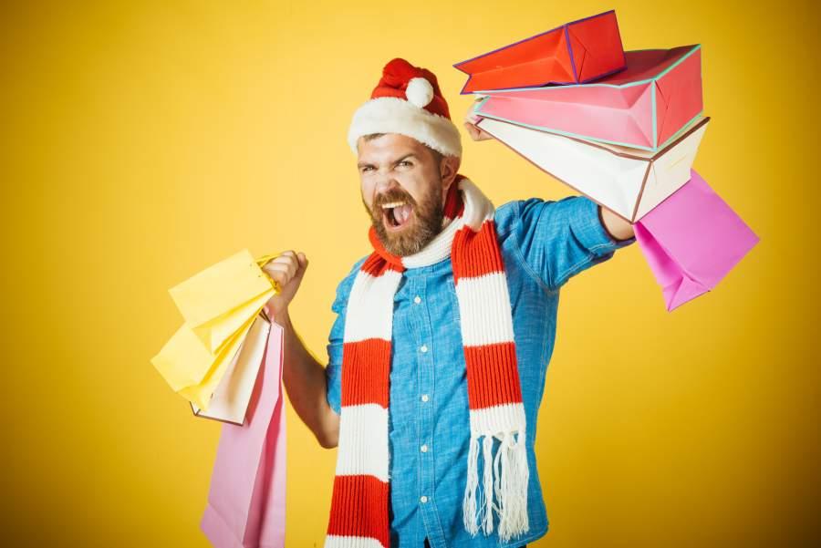 Mann, Weihnachten, Einkaufstüten, Weihnachtsmütze, Schal, rot/weiß, blaues Hemd, gelber Hintergrund, Kauflaune, Weihnachten in Deutschland 2017