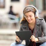 junge Frau, Lächeln, Jacke, draußen, Innenstadt, Kopfhörer, Tablet, Streaming, Live Streaming, Video Streaming, erfolgreiches Video Content Marketing 2018