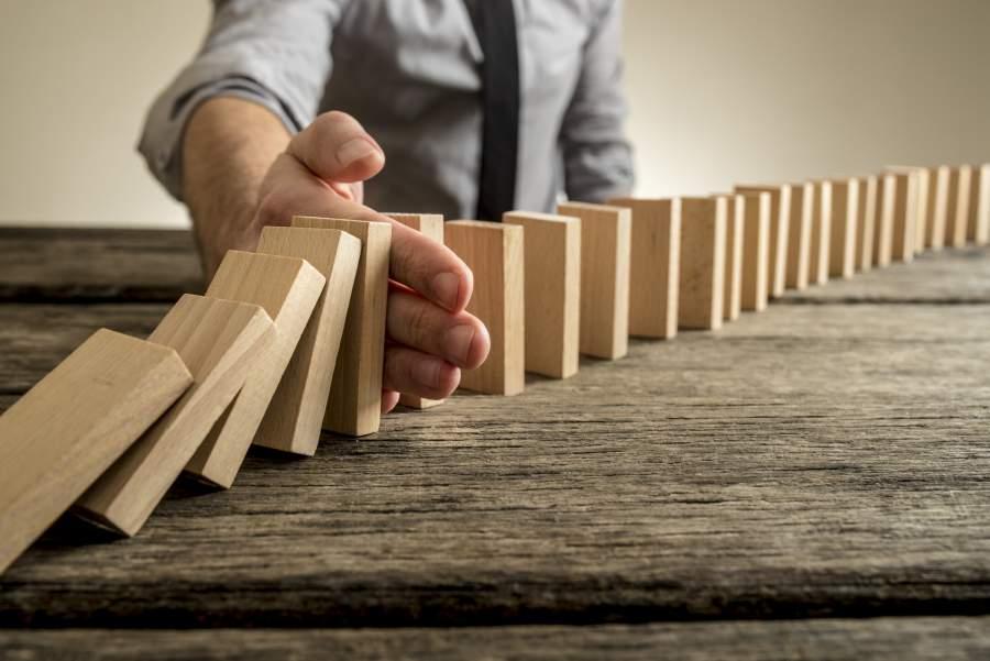 Domino-Effekt, Dominosteine, Geschäftsmann, Krawatte, Machtwort, Intervention, Eingreifen, Katastrophen verhindern, VOraussicht, unternehmreische Weitsicht, Langfristiger Erfolg, erfolgreich langfristig planen
