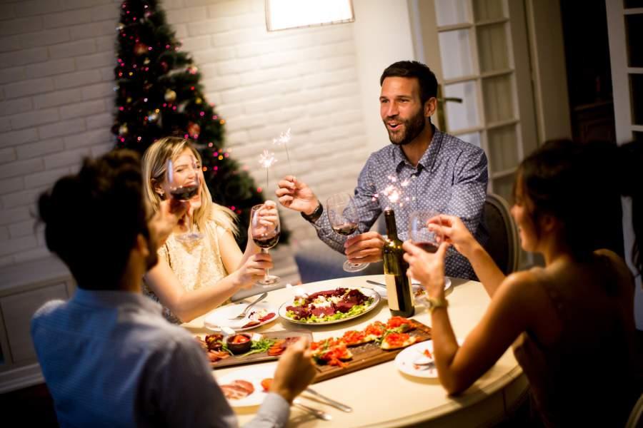 Weihnachtsessen, Wunderkerzen, Weihnachtsbaum, gedeckter Tisch, Weihnachtsessen, Menschen, Wein, Anstoßen, Feiern, das richtige Verhalten auf der Weihnachtsfeier