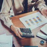 Mann, Schreibtisch, Taschenrechner, Statistiken, Werte, Berechnung, Kalkulation, Konkurrenzfähigkeit von Wirtschaftsstandorten