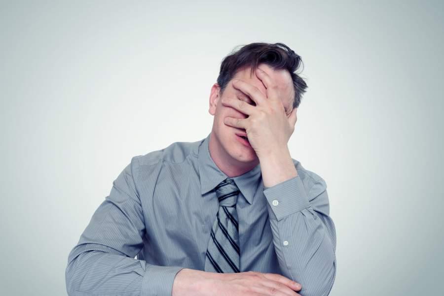 Geschäftsmann, Facepalm, Hand am Gesicht, Kopf abstützen, falsche Gestik in Präsentationen, Körpersprache lesen, nonverbale Kommunikation, negative Körpersprache Beispiele