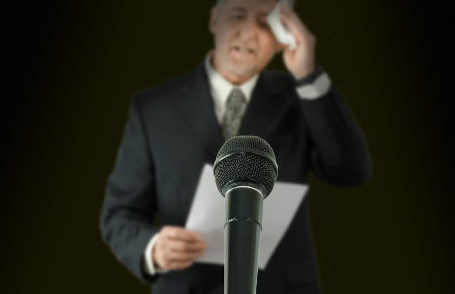 Mikrofon, Mann, Vortrag, Lampenfieber, Nervosität, Ansprache, Schweißausbruch, kalter Schweiß, Angstgefühl, Notizen, Stress, No-Gos im Vortrag, Dos und Don'ts im Vortrag, unbewusste Körpersprache, richtige und falsche Gestik in der Präsentation