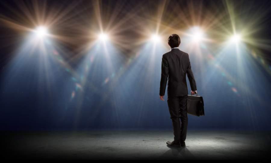 Geschäftsmann, Bühne, Publikum, Scheinwerfer, Aktenkoffer, Konfrontation, Rede halten, Keynote Speaker, Tipps für Selbstsicherheit im Vortrag, selbstsicher vor Publikum auftreten