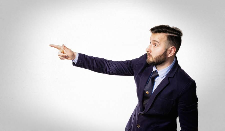 Mann, Anzug, Überraschung, Überforderung, Fingerzeig, richtige Gestik für Präsentation, Hinweis, Zeigefinger, Handgriffe, wirkungsvolle Körpersprache im Vortrag