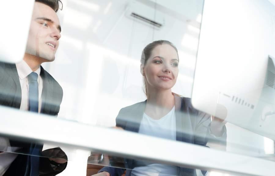 Mitarbeiter, Mann, Frau, Kollegen, Mitarbeiter, Desktop, Shreibtisch, Fenster, Glasscheibe, Lächeln, Bildschirmarbeit, Compliance, Transparenz, Prozessdokumentation, Prozesshandbuch, personenbezogene Daten, Zugriffsrechte, EU DSGVO, BDSG, wann Unternehmen einen Datenschutzbeauftragten benötigen, Sensibilisieren