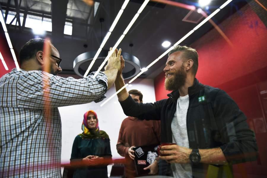 High-five, Handschlag, Jubeln, Erfolg feiern, Arbeitskollegen, Tasse, Pause, Anlass, Mitarbeiter motivieren, Mitarbeitermotivation steigern, Loyalität fördern