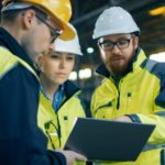 Drei Mitarbeitende in Sicherheitskleidung und Schutzhelmen diskutieren Fakten auf einem Tablet in der Maschinenhalle