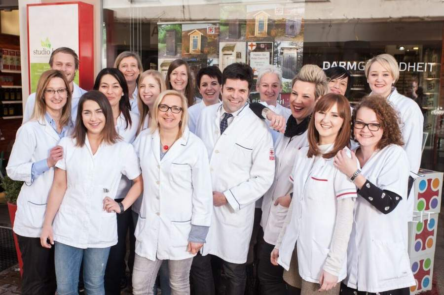Dr. Klaus Schirmer mit seinen Mitarbeitenden vor seiner Apotheke als herzliches und freundschaftliches Team