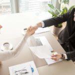 Geschäftsfrau und Geschäftsmann sitzen am Tisch mit Handshake, vor ihnen liegen Unterlagen in einem hellen Besprechungszimmer, sie lächeln