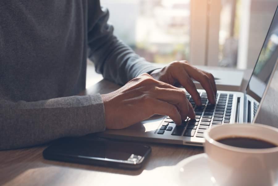 Geschäftsmann arbeitet an Laptop an Holztisch, neben sich ein Smartphone und eine Tasse Kaffee