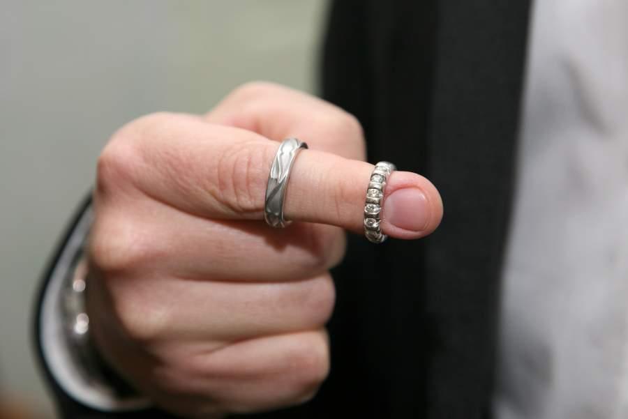 Zwei edle Ringe mit Verzierung und Diamanten auf dem Zeigefinger einer Business-Person