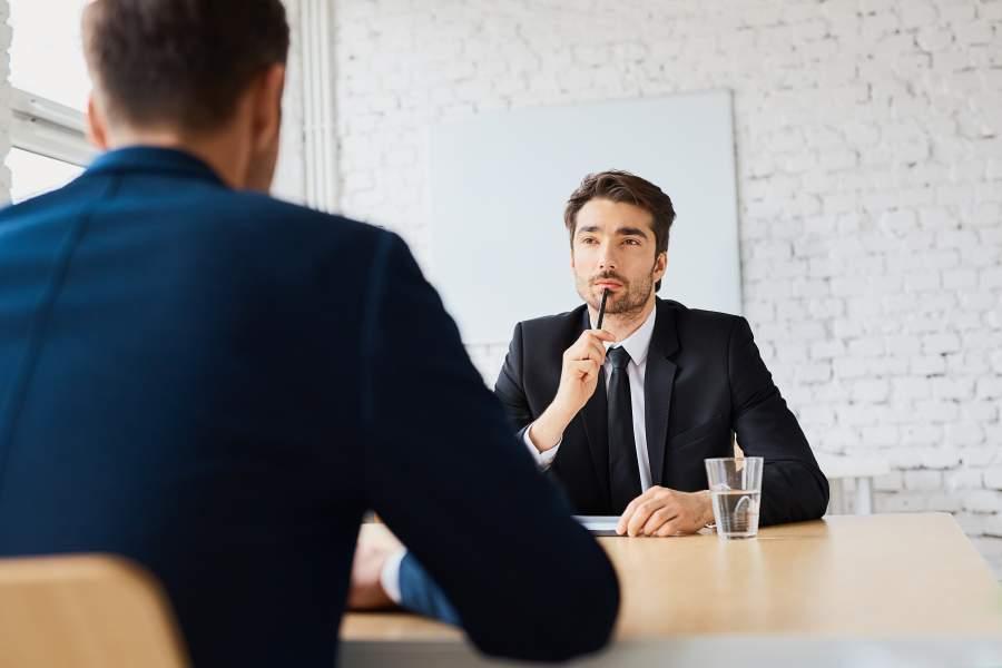 Zwei Geschäftsmänner sitzen sich im Meetingraum gegenüber und sehen sich an, einer hält den Stift an den Mund in überlegender Geste