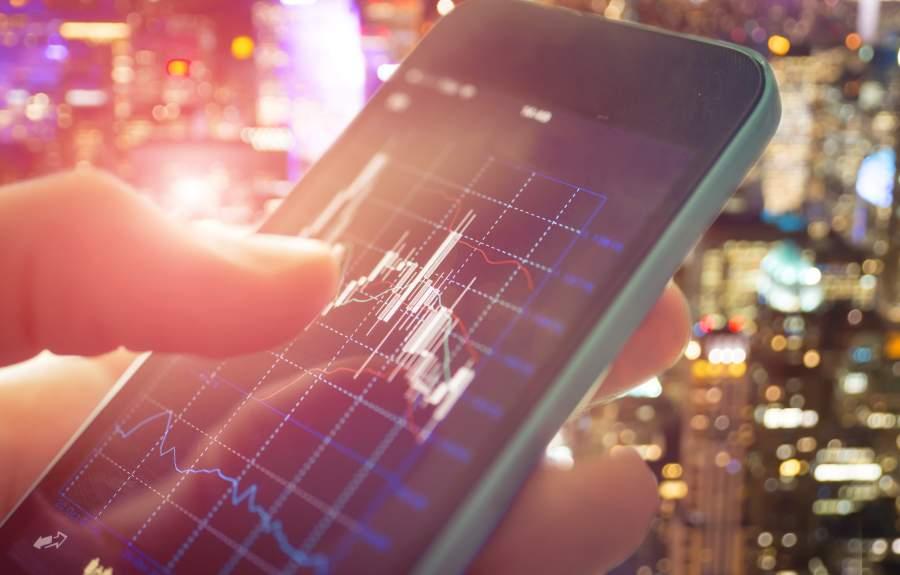 Graph auf dem Smartphone in der Hand zeigt Wechselkurs zweier Währungen im Forex-Handel an