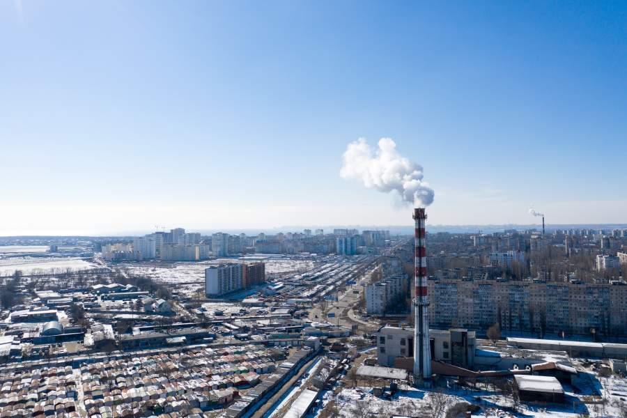 Kleine Rauchwolke an einem hohen Kamin über einem Industriegelände mit Parkplatz in der Nähe vor einem klaren blauen Himmel