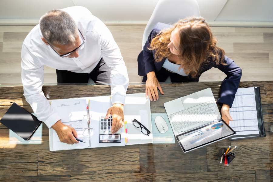 Frau und Mann an Holztisch im Steuerberater-Erstgespräch mit Unterlagen, Taschenrechner, Lesebrille und Laptop im Gespräch, Vogelperspektive