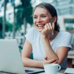 Junge digitale Nomading sitzt im Freien mit Laptop, Kaffeetasse und Stift bei der Arbeit und lacht, während sie den Blick schweifen lässt