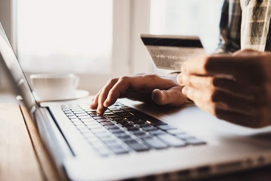 Mann sitzt mit Kreditkarte in seiner linken Hand vor seinem Laptop in einem lichtdurchfluteten Raum und tippt mit der rechten Hand.