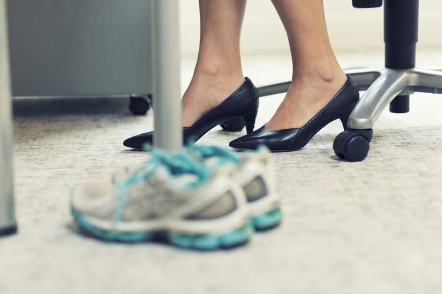 Laufschuhe oder Sportschuhe auf dem Teppich neben dem Büroarbeitsplatz, daneben sind die Füße einer Geschäftsfrau in schwarzen Business-Schuhen mit Absatz zu sehen