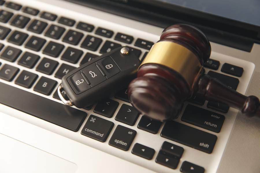 Autoschlüssel und Richter- oder Auktionshammer liegen auf der Tastatur eines Laptops