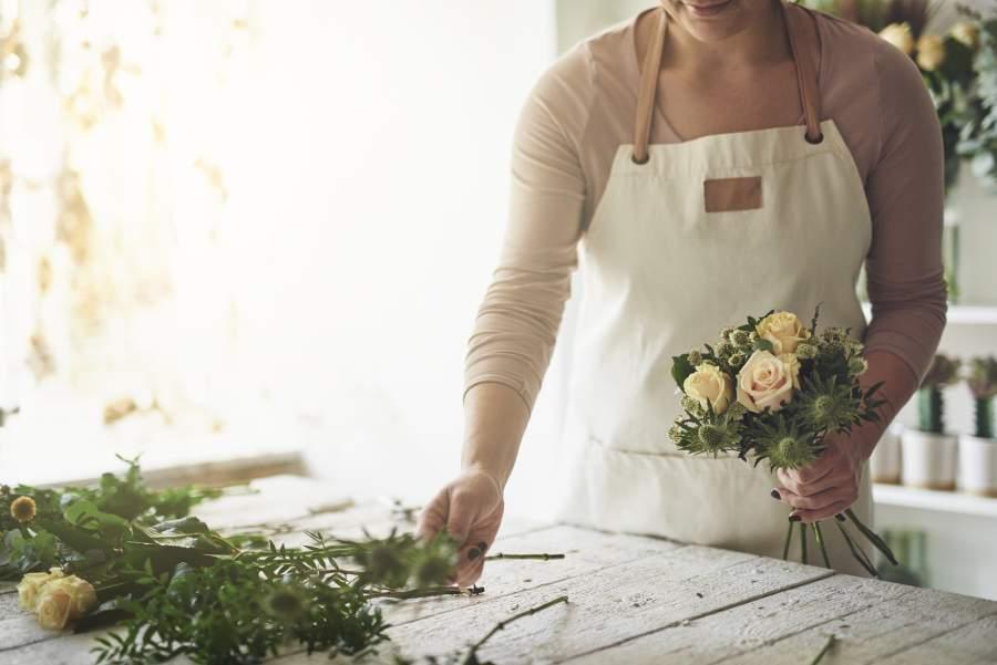 Floristin mit weißer Schürze macht einen frischen Blumenstrauß mit weißen Rosen in einem freundlichen, hellen Blumenladen