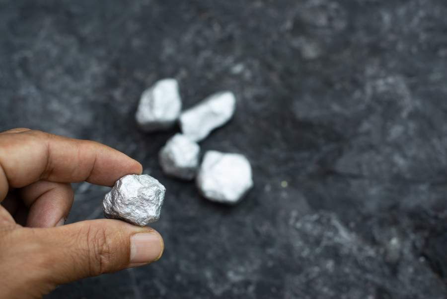 Bröckchen Platin, gehalten von einer männlichen Hand auf dunklem Steinhintergrund