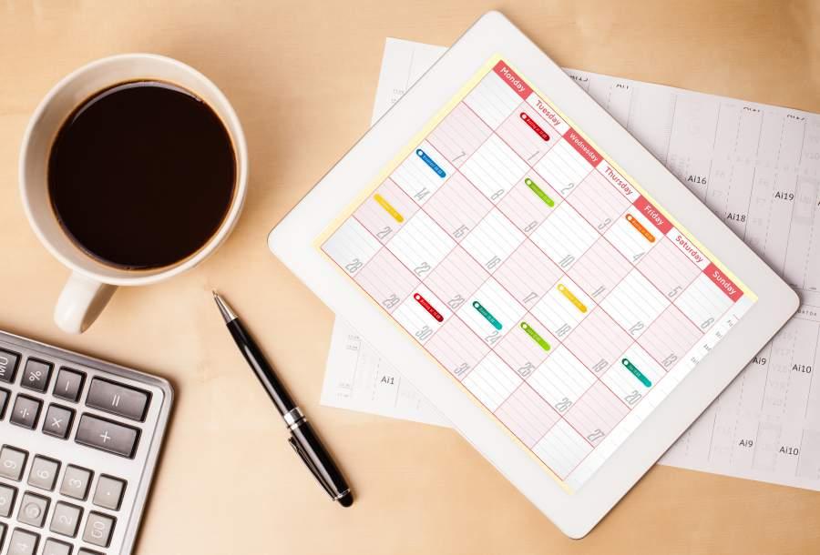 Tablet mit Kalender in Monatsansicht liegt auf einem Tisch, daneben ein Kugelschreiber, eine volle Tassee Kaffee und eine Computertastatur