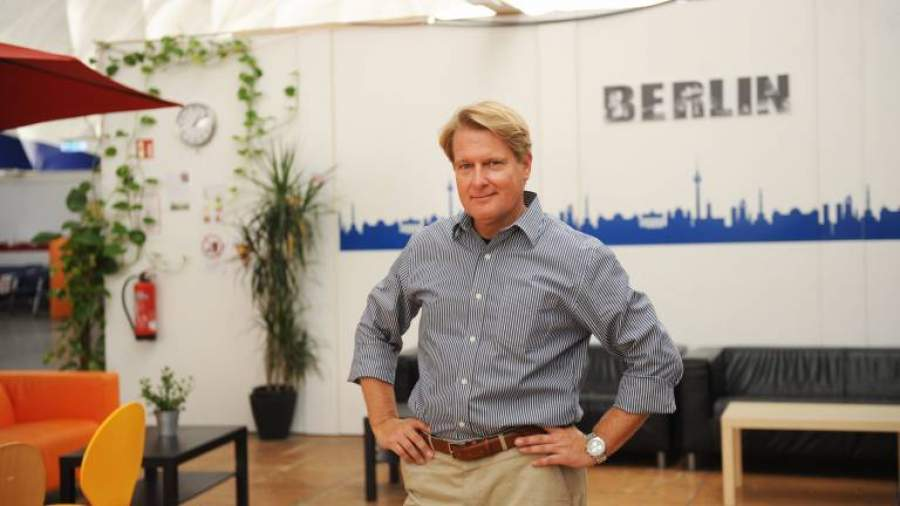 Jürgen Wowra, Geschäftsführer von PARANET, steht in blau-weiß gestreiftem Hemd vor einer weißen Wand mit der Aufschrift Berlin.