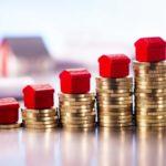 Fünf rote Monopoly-Häuschen stehen nebeneinander aufgereiht auf einem jeweils immer größer werdenden Münzturm.