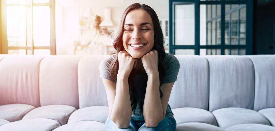 Brauhaarige Frau sitzt auf grauem Sofa und lächelt, das Gesicht auf die Hände gestützt mit geschlossenen Augen.