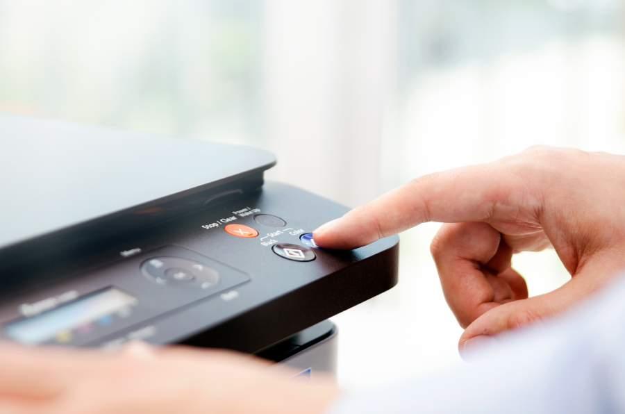 Rechte Hand einer Person drückt auf die Starttaste eines Druckers.