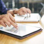 Touchscreen-Tablet und Laptop auf einem Schreibtisch werden jeweils mit einer Hand einer Person bedient